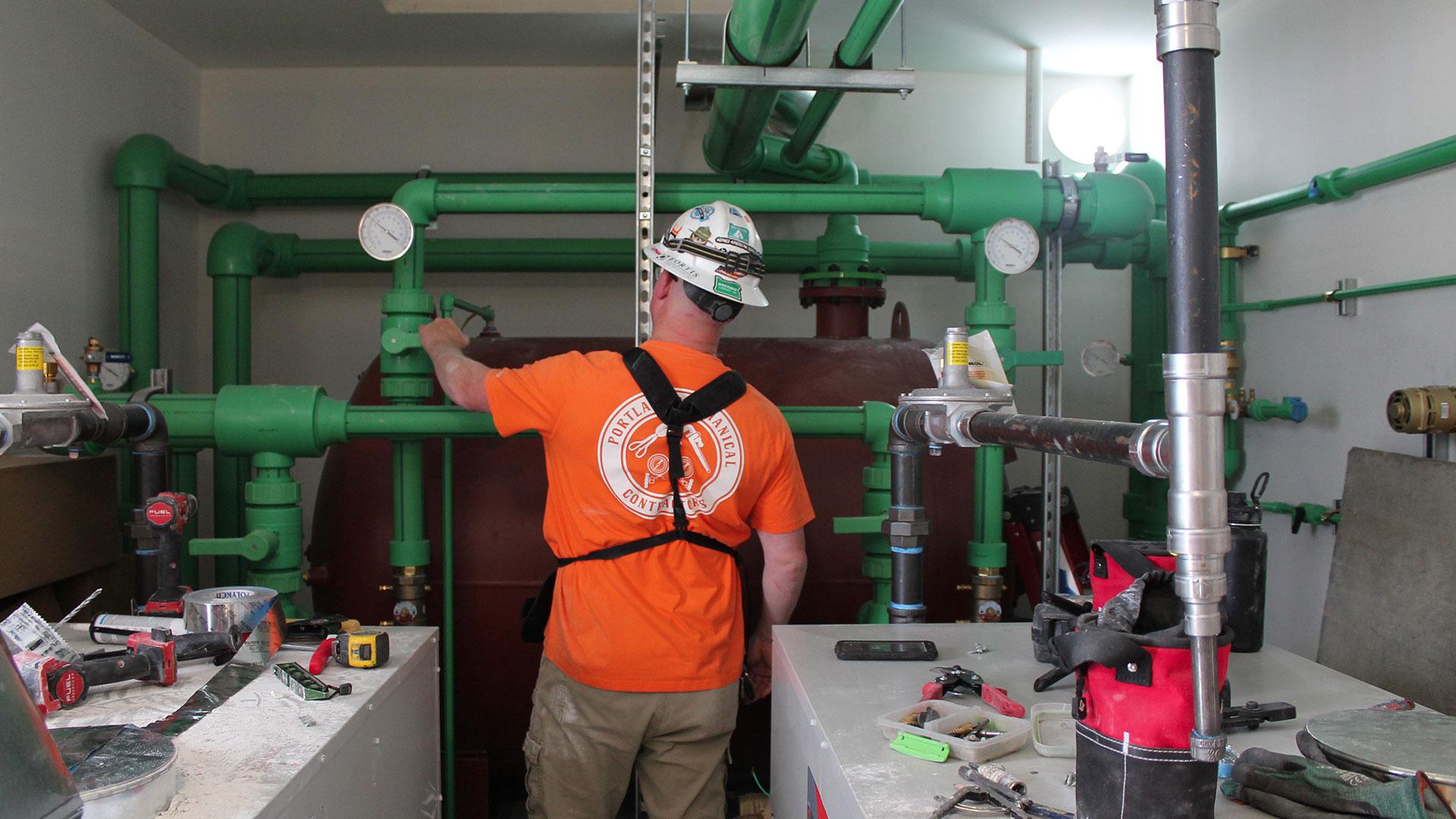 Employee in hard hat inspecting plumbing